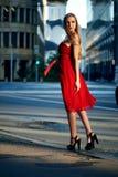 Schöne blonde Dame im roten Kleid auf weißem Quadrat Stockbilder