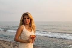 Schöne blonde Dame mit einem Glas Roséwein durch Küste Stockfotografie