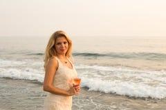 Schöne blonde Dame mit einem Glas Roséwein durch Küste Stockfoto