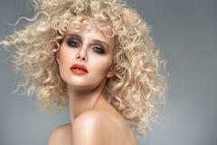 Schöne blonde Dame mit herrlicher gelockter Frisur Lizenzfreie Stockfotografie