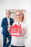 Schöne blonde Dame verkauft ihr Haus Stockfotografie