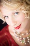 Schöne blonde Dame, welche die Kamera betrachtet Stockfoto