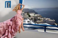 Schöne blonde Durchgehenbraut im weißen Hochzeitskleid fabelhaft mit einem sehr langen Zug von Kristallen in der Straße auf Santo Lizenzfreies Stockfoto