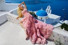 Schöne blonde Durchgehenbraut im weißen Hochzeitskleid fabelhaft mit einem sehr langen Zug von Kristallen in der Straße auf Santo Lizenzfreie Stockfotografie