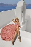 Schöne blonde Durchgehenbraut im weißen Hochzeitskleid fabelhaft mit einem sehr langen Zug von Kristallen in der Straße auf Santo Stockfoto
