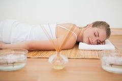 Schöne blonde Entspannung auf Bambusmatte Lizenzfreie Stockfotos