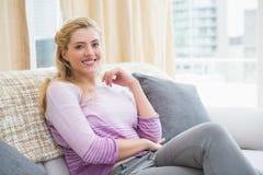 Schöne blonde Entspannung auf der Couch Stockfotos