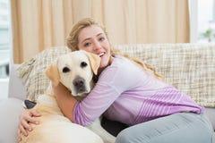 Schöne blonde Entspannung auf der Couch mit Schoßhund Lizenzfreies Stockbild