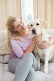 Schöne blonde Entspannung auf der Couch mit Schoßhund Lizenzfreie Stockbilder