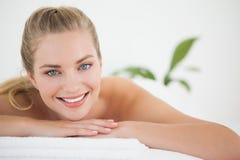 Schöne blonde Entspannung auf der Massagetabelle, die an der Kamera lächelt Lizenzfreie Stockfotografie