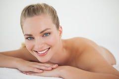 Schöne blonde Entspannung auf der Massagetabelle, die an der Kamera lächelt Stockbild