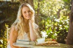 Schöne blonde Entspannung mit einem Buch und einem Lebensmittel Lizenzfreie Stockbilder