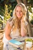 Schöne blonde Entspannung mit einem Buch und einem Lebensmittel Stockbild