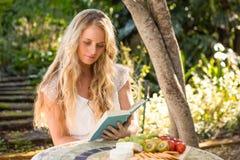Schöne blonde Entspannung und Ablesen mit Lebensmittel Lizenzfreie Stockfotos
