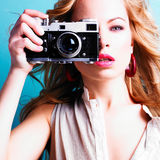 Schöne blonde Fotograffrau, die Retro- Kamera hält Stockfotografie
