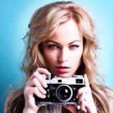Schöne blonde Fotograffrau, die Retro- Kamera hält Lizenzfreie Stockfotos