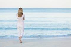 Schöne blonde Frau alleine am Strand Lizenzfreie Stockbilder