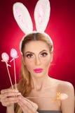 Schöne blonde Frau als Osterhase mit den Hasenohren auf rotem Hintergrund, Atelieraufnahme Junge Dame, die drei farbige Eier hält Stockbild