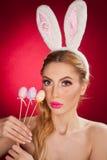 Schöne blonde Frau als Osterhase mit den Hasenohren auf rotem Hintergrund, Atelieraufnahme Junge Dame, die drei farbige Eier hält Stockfoto