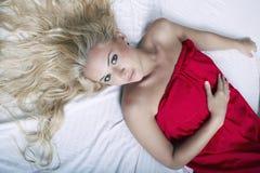 Schöne blonde Frau auf dem Bett Stockbilder