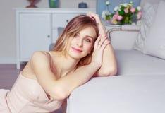Schöne blonde Frau auf dem Sofa Lizenzfreie Stockfotos