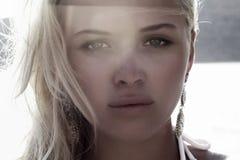 Schöne blonde Frau auf dem Strand. Licht auf dem Gesicht. Sonnenuntergang Lizenzfreie Stockfotos