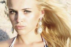 Schöne blonde Frau auf dem Strand. Licht auf dem Gesicht. Sonnenuntergang Stockbilder