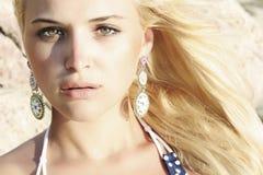 Schöne blonde Frau auf dem Strand. Licht auf dem Gesicht. Sonnenuntergang Stockfotos
