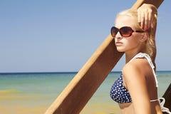 Schöne blonde Frau auf dem Strand. Treppe zum Meer Stockfotografie