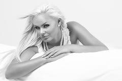 Schöne blonde Frau auf einem Bett Lizenzfreies Stockfoto