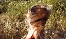 Schöne blonde Frau auf einem Weizengebiet bei Sonnenuntergang Stockbilder