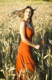 Schöne blonde Frau auf einem Weizengebiet bei Sonnenuntergang Lizenzfreies Stockbild