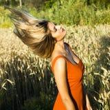 Schöne blonde Frau auf einem Weizengebiet bei Sonnenuntergang Stockbild