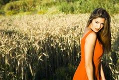 Schöne blonde Frau auf einem Weizengebiet bei Sonnenuntergang Lizenzfreie Stockfotos