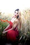 Schöne blonde Frau auf einem Weizengebiet mit Mohnblumen bei Sonnenuntergang Lizenzfreie Stockbilder