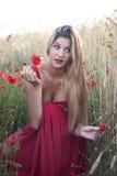 Schöne blonde Frau auf einem Weizengebiet mit Mohnblumen bei Sonnenuntergang Lizenzfreies Stockfoto
