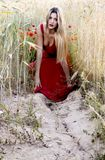 Schöne blonde Frau auf einem Weizengebiet mit Mohnblumen bei Sonnenuntergang Stockfotografie