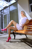 Schöne blonde Frau auf einer Bank stockfotografie