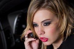 Schöne blonde Frau auf ihrem Handy Stockfotografie