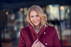 Schöne blonde Frau beim Kirschrot-Mantellächeln Stockbild