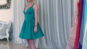 Schöne blonde Frau demonstriert TürkisCocktailkleid Spinnen in rote Sandalen im weißen Bekleidungsgeschäft stock video footage