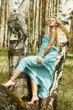 Schöne blonde Frau in den rosa Schuhen auf einem Baum Stockbild