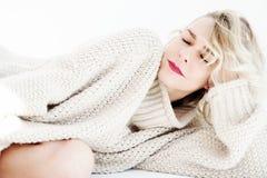 Schöne blonde Frau in der beige Strickjacke, die im Bett liegt Stockfotos