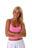 Schöne blonde Frau in der Eignung kleidet die gefalteten Arme Stockfoto