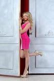 Schöne blonde Frau an der geöffneten Tür. Stockfotografie