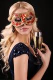 Schöne blonde Frau in der Karnevalsmaske, mit Glas Champagner Lizenzfreies Stockfoto