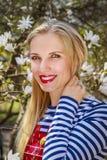 Schöne blonde Frau in der Park Magnolienblume Stockfotos