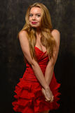 Schöne blonde Frau in der roten Kleiderstellung verbog Armverschluß Lizenzfreies Stockfoto
