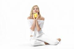 Schöne blonde Frau in der weißen Bluse, die gelben grünen Pfeffer hält Gesunde Diät und Diät Stockfoto