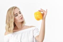 Schöne blonde Frau in der weißen Bluse, die gelben grünen Pfeffer hält Gesundheit und Diät Stockbild